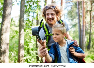 Happy young man and his son with compass orienting in the forest during trip