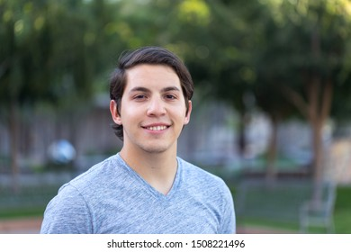 Happy young man Hispanic college student outside