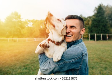 Happy young man holding dog Labrador in hands at sunset outdoors