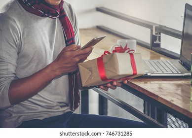 Happy young man holding present in christmas time