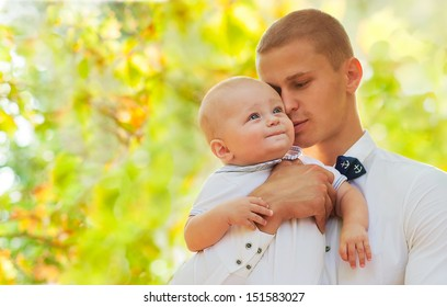 Happy young man holding a smiling 7-9 months old baby