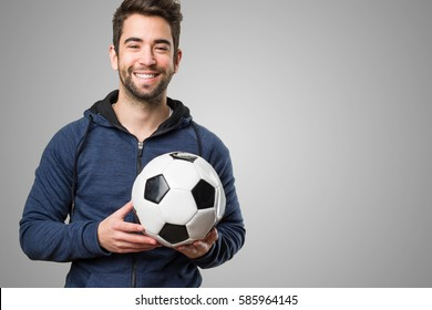 happy young man holding a soccer ball