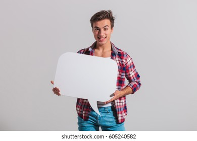 happy young man holding speech bubble and smiles on grey background