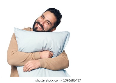 Happy young man in home clothes hugging pillow over white background
