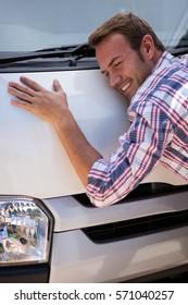 Happy young man hugging his car