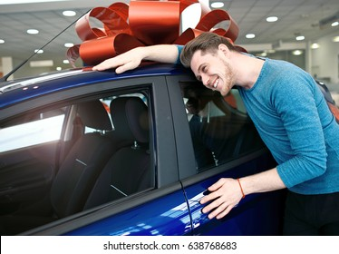 Happy young man is hugging his first brand new car.