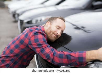 A Happy young man hugging his car outside of garage shop