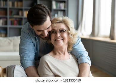 Happy young man hugging mature mother wearing glasses from back, expressing love and gratitude, adult son and middle aged woman cuddling, family enjoying tender moment, sitting in living room at home