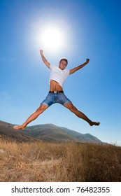 Happy young man jump in the mountains looking at camera