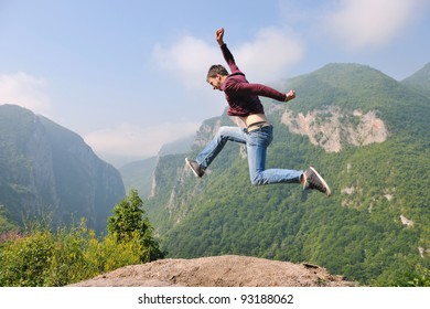 happy young man jump in nature while representing healthy lifestyle freedom and active concept