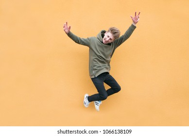 Happy young man jumping against the background of an orange wall. The leap of an emotional student on a bright colored background.