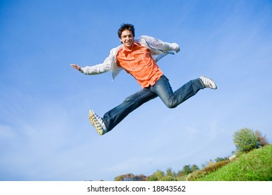 Happy young man - jumping  against the backdrop of blue sky.
