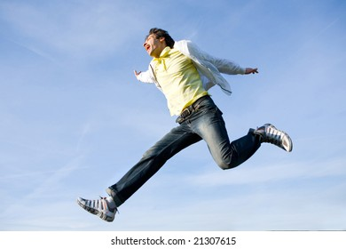Happy young man - jumping  end flies in blue sky