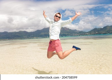 happy young man jumping of joy on the beach of seychelles