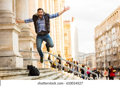 happy young man jumping up for joy on the stairs of a building with large columns, celebrating a big victory or celebrating a big victory or achievement, celebrating passing exams