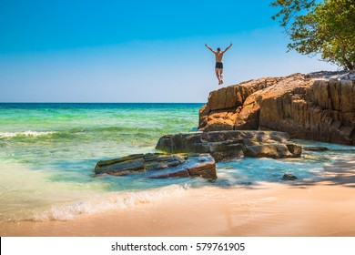 The happy young man jumping off cliff into the ocean. Summer fun, lifestyle, extreme sport.