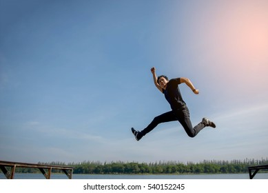Happy young man jumping on the waterfront dock.