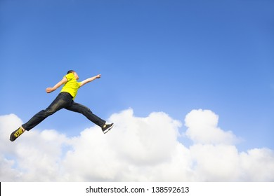 happy young man jumping and pointing to sky
