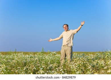 The happy young man jumps in the field of chamomiles