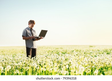Happy young man with laptop in hand standing on meadow with dandelions