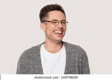 Happy young man laughing at funny joke squinting his eyes. Sincere laughter of attractive male with beautiful smile isolated on grey background in photo studio. Positive funny advertising concept