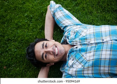 Happy young man lying in grass
