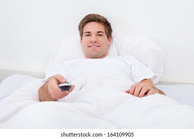 Happy Young Man Lying On Bed Watching Television