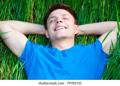 happy young man lying on the green grass