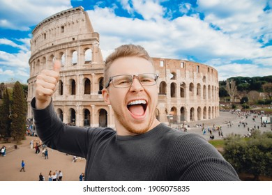 Happy young man making selfie thumb up sign in front of Colosseum in Rome, Italy. Concept travel trip.