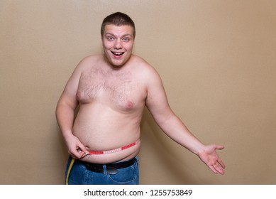 Happy young man measures his fat belly with a meter