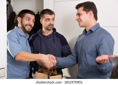 Happy young man meeting male friends and gladly inviting to apartment