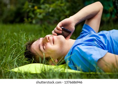 Happy Young Man with a Mobile Phone on the Grass outdoor