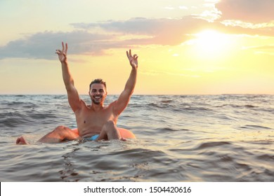 Happy young man on inflatable ring in water