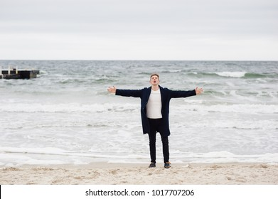 a happy young man is on the shore of the ocean joyfully placed his hands on both sides and inhales the air full of chest