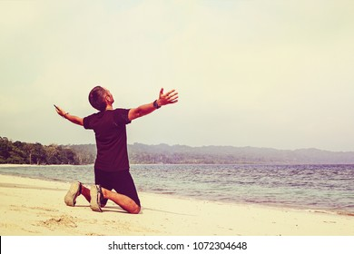 happy young man on the tropical white sand tropical beach rising up hands. guy kneels with his hands up to the sky. sun, travel, vacation, water, activity,
