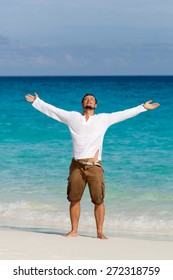 happy young man on the tropical white sand beach