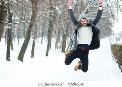 happy young man on winter park jumping have joy