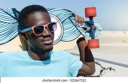 Happy young man outdoors holding his skateboard