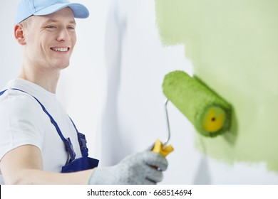 Happy and young man is painting a wall green