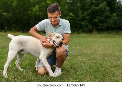 Happy young man is playing with dog Labrador