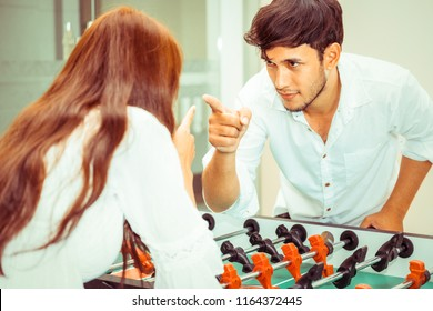 Happy young man playing foosball table soccer with girlfriend. Couple recreation and lifestyle.