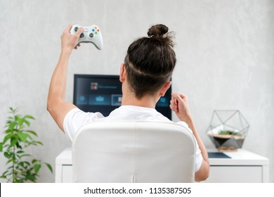 Happy young man playing and winning online game on computer. Back view of gamer with video console gamepad controller. Competitive gaming, electronic sports, technology, gaming, entertainment concept.