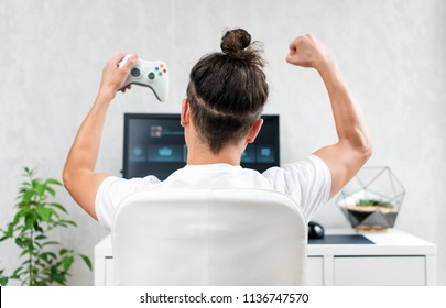 Happy young man playing and winning online game on computer. Back view of gamer with video console gamepad controller. Competitive gaming, electronic sports, technology, gaming, entertainment concept
