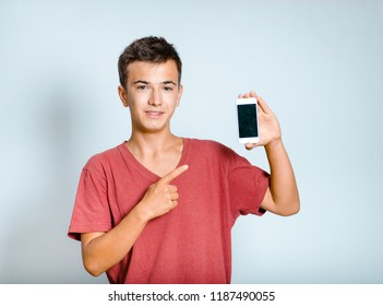 Happy young man points a finger at the smartphone, isolated studio photo on the background