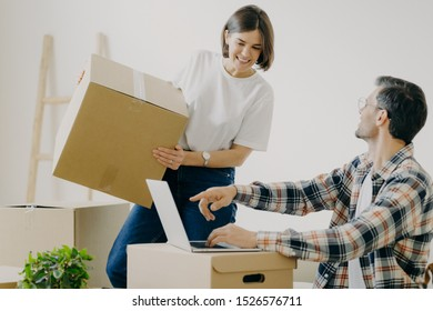 Happy young man points into laptop computer, searches new design for flat, busy woman carries boxes, makes purchase on new habitation, search home decorations, connected to wirless internet.