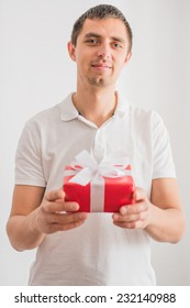 happy young man poses with a gift in his hands