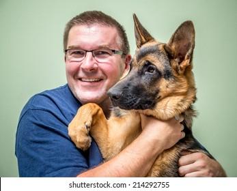 Happy young man posing with its German shepherd pet