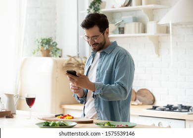 Happy young man preparing romantic dinner searching vegetable recipes diet menu cookbook app using smartphone, smiling husband holding phone cooking healthy vegan food cut salad in kitchen interior