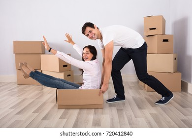 Happy Young Man Pushing The Woman Sitting On Cardboard Box At Home