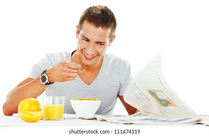 happy young man reading newspaper while having energetic breakfast